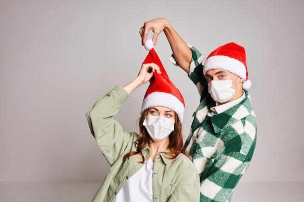 Familienpaar in medizinischen masken auf dem gesicht der weihnachtsmütze neujahrswinterumarmungen