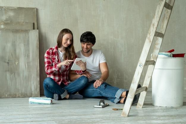 Familienpaar mit digitalem tablet während der renovierung im neuen haus junges paar sitzt auf dem boden und benutzt ein tablet in einem neuen zuhause