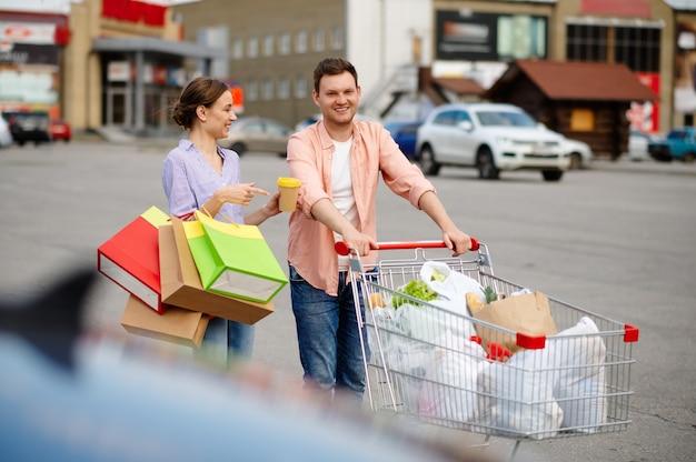 Familienpaar mit taschen im warenkorb auf dem parkplatz des supermarkts. zufriedene kunden, die einkäufe aus dem einkaufszentrum tragen, fahrzeuge im hintergrund