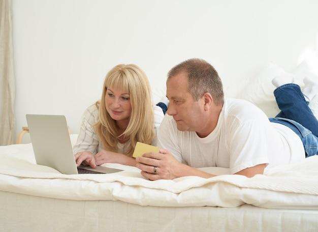 Familienpaar sitzt im bett und macht online-einkäufe