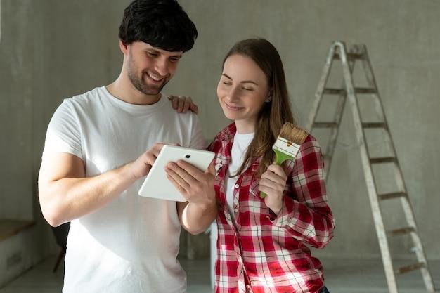 Familienpaar steht und benutzt ein tablet und wählt proben für reparaturen zu hause aus