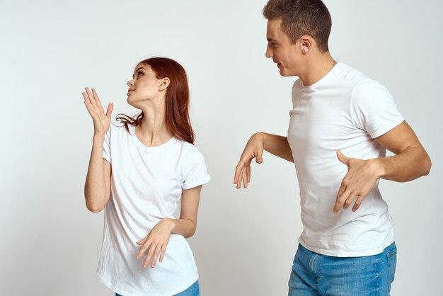 Familienpaar verliebt jeans weißes t-shirt emotionen lustiger mann und frau, die spaß auf einem hellen raum haben, der mit ihren händen gestikuliert.