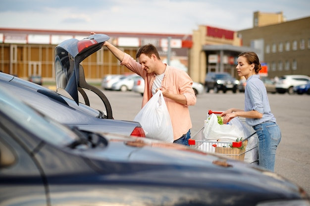 Familienpärchen legt seine einkäufe in den kofferraum