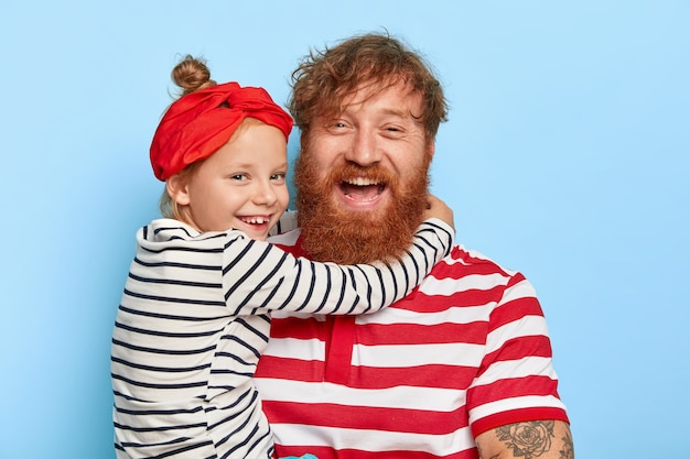 Familienporträt der glücklichen tochter trägt rotes stirnband und gestreiften pullover, umarmt entzückten vater mit dickem ingwerbart und lockigem haar, lieben sich sehr