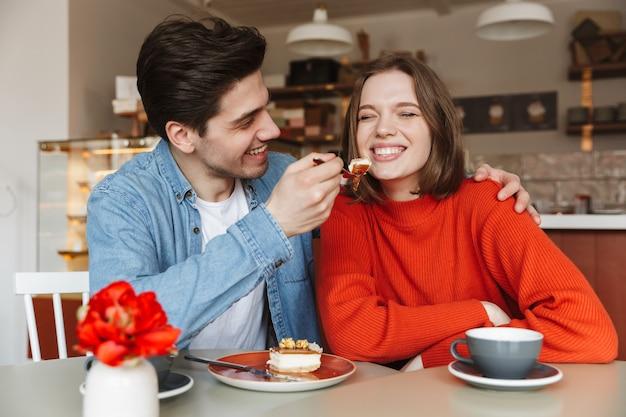 Familienporträt des glücklichen paares, das süßigkeiten isst, während mann frau mit leckerem kuchen im café füttert