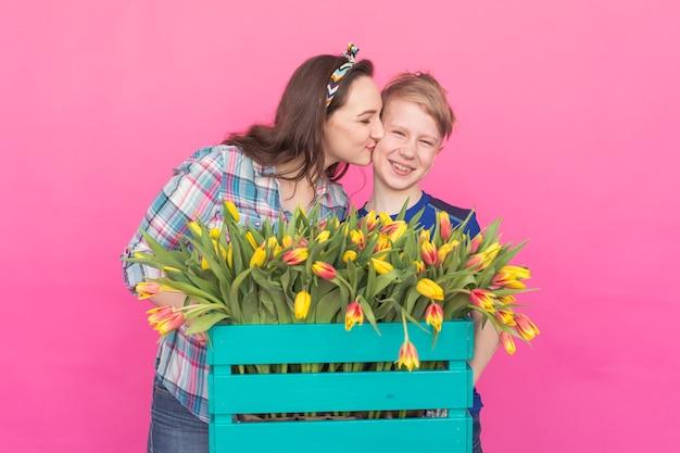 Familienporträt schwester und teenager bruder mit tulpen auf rosa hintergrund