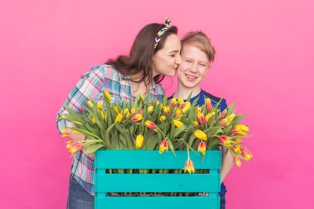 Familienporträt schwester und teenager bruder mit tulpen auf rosa wand