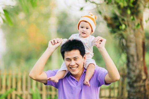 Familienporträt von 6 monaten baby, das mit ihrem vater im garten glücklich sich fühlt