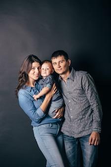 Familienporträt von eltern und kind in der freizeitkleidung des denims. modemodelle, die kamera auf grauem hintergrund betrachten.