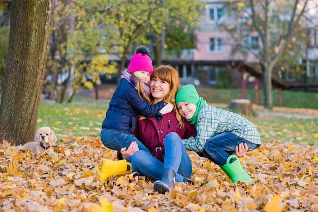 Familienporträt von frau und kindern sitzen am laub