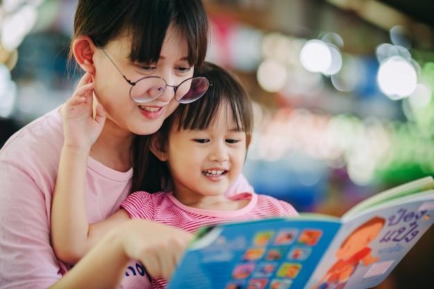 Familienporträt von mutter und kindern, die ein buch zusammen lesen.