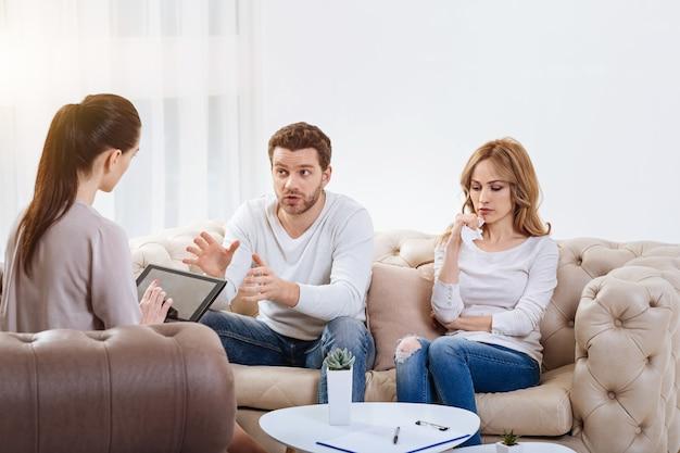 Familienprobleme. nette freudlose blonde frau, die neben ihrem ehemann sitzt und ein taschentuch hält, während sie mit ihm einen psychologen besucht