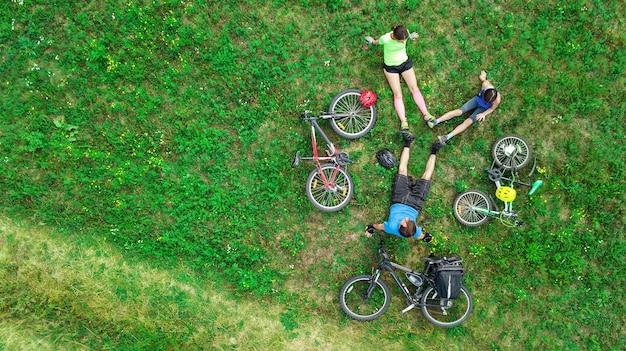 Familienradfahren auf fahrrädern luftaufnahme von oben, glückliche aktive eltern mit kind haben spaß und entspannen sich auf gras, familiensport und fitness am wochenende