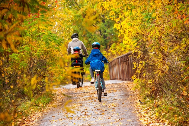 Familienradfahren im goldenen herbstpark, aktiver vater und kinder fahren fahrrad, familiensport und fitness mit kindern im freien