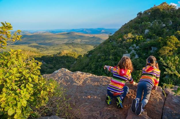 Familienreise mit kindern, kinder, die vom bergstandpunkt, feiertagsferien in südafrika schauen