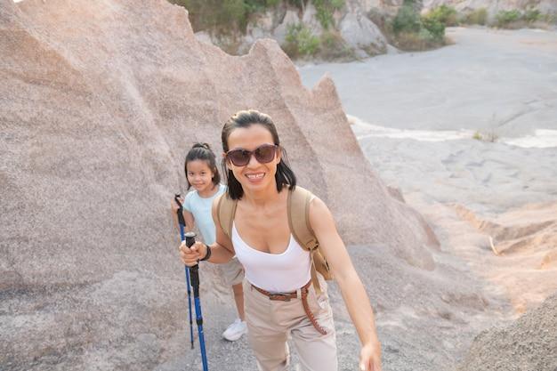 Familienreisende mit rucksack mit blick auf die berge, mutter mit kind tagsüber.