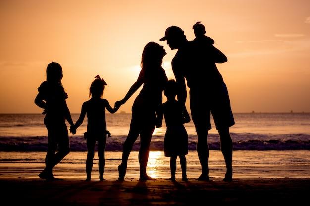 Familienschattenbild am sonnenuntergangsstrand.