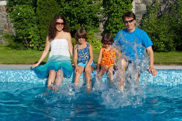 Familiensommerferien. glückliche eltern mit zwei kindern, die spaß haben und nahe swimmingpool spritzen. urlaub mit kindern