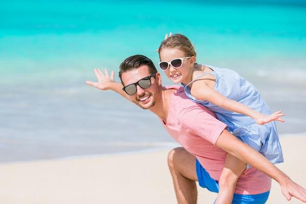 Familienspaß auf weißem sand. lächelnder vater und entzückendes kind, die am sandigen strand an einem sonnigen tag spielen