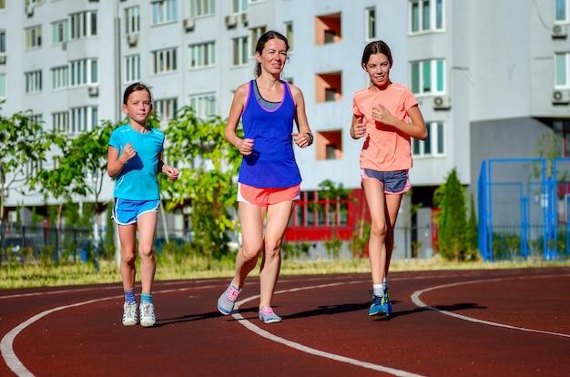 Familiensport und eignung, glückliche mutter und kinder, die draußen auf stadionsbahn laufen, kindergesundes aktives lebensstilkonzept