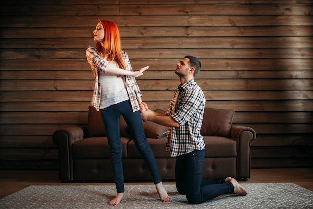 Familienstreit, ehemann und ehefrau in konflikt, mann auf den knien entschuldigt sich. problembeziehung, paar in stress