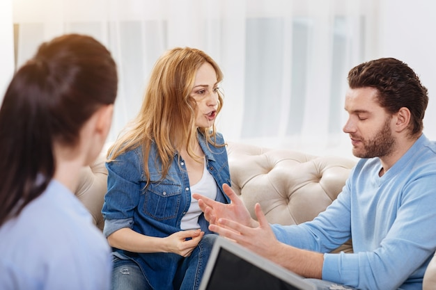 Familienstreit. wütende wütende junge frau, die ihren ehemann ansieht und schreit, während sie sich mit ihm streitet