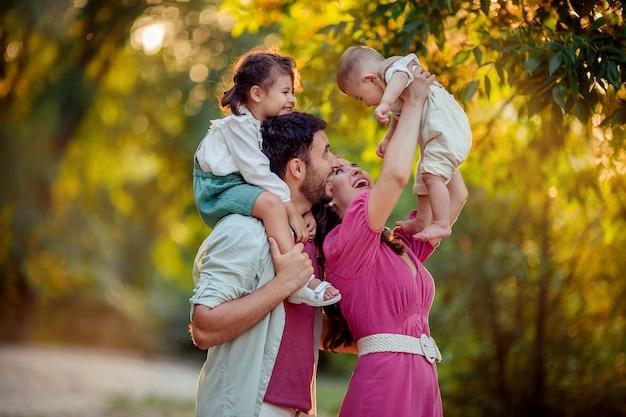 Familientag! glückliche eltern mama und papa halten ihren sohn und ihre tochter in den armen ihrer kleinen kinder. sie lachen und haben spaß im sommer bei einem spaziergang im park