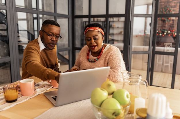 Familientreffen. netter angenehmer mann, der mit seiner schwester sitzt und auf den laptopbildschirm zeigt