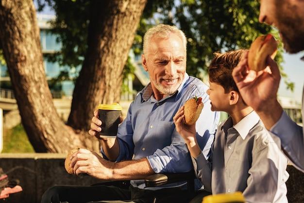 Familientreffen sohn und enkel sitzen auf der bank