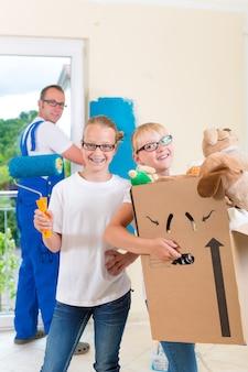 Familienumzug mit kisten voller sachen, sie streichen die wände ihres neuen hauses
