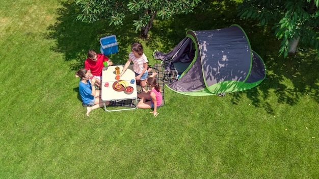 Familienurlaub auf dem campingplatz luftaufnahme von oben, eltern und kinder entspannen sich und haben spaß im park, zelt und campingausrüstung unter baum, familie im camp im freien konzept
