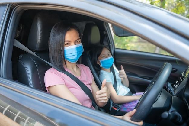Familienurlaub, coronavirus covid-19 und gesichtsmaske, mutter mit stoffgesichtsmaske für kleine mädchentochter, wenn. neue normale bleib sicher. sommerfahrt mit dem auto.