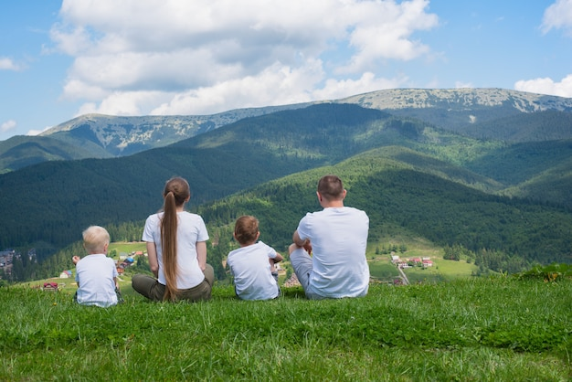 Familienurlaub. eltern und zwei söhne bewundern die aussicht auf die berge. rückansicht. sonniger sommertag