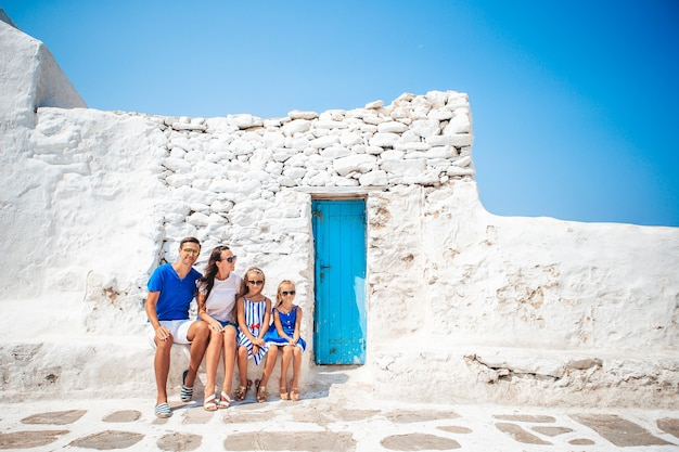 Familienurlaub in europa. eltern und kinder an der straße des typischen griechischen traditionellen dorfes mit weißen wänden und bunten türen auf der insel mykonos in griechenland