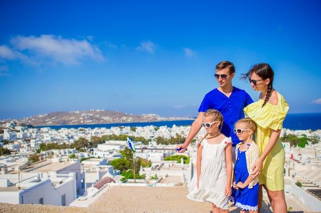 Familienurlaub in europa. eltern und kinder, die selfie fotohintergrund mykonos-stadt in griechenland nehmen