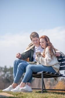 Familienurlaub. junger erwachsener fürsorglicher mann, der mit decke bedeckt und lächelnde frau mit katze sitzt auf der bank in der natur