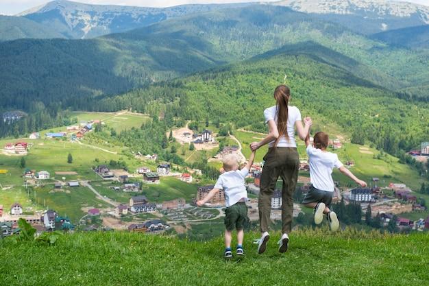 Familienurlaub. mutter mit söhnen springen auf den hintergrund der berge