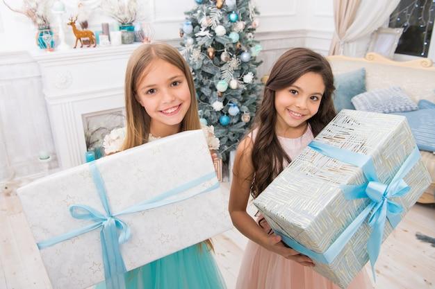 Familienurlaub. nettes kleines kindermädchen mit weihnachtsgeschenk. glückliche kleine mädchenschwestern feiern winterurlaub. weihnachtszeit. frohes neues jahr. lieferung weihnachtsgeschenke. vorbereitung auf weihnachten.