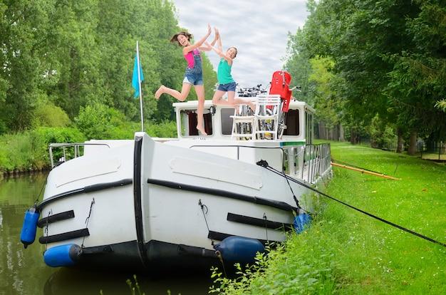 Familienurlaub, reisen auf lastkahnboot im kanal, glückliche eltern mit den kindern, die spaß auf flusskreuzfahrtreise im hausboot haben