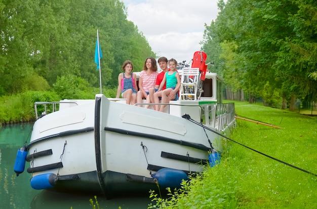 Familienurlaub, sommerferienreise auf lastkahnboot im kanal, glückliche kinder und eltern, die spaß auf flusskreuzfahrt im hausboot in frankreich haben