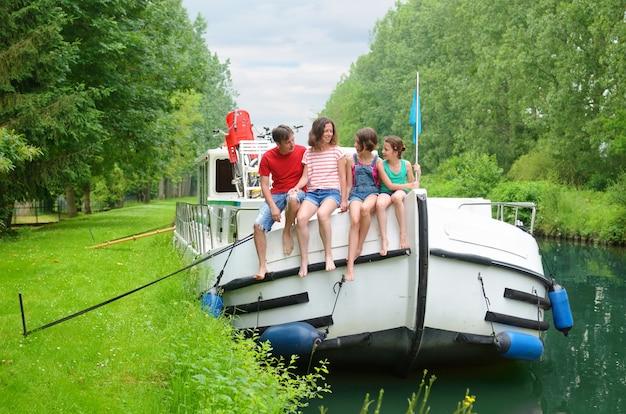 Familienurlaub, sommerferienreise auf lastkahnboot im kanal, glückliche kinder und eltern, die spaß auf flusskreuzfahrtreise im hausboot in frankreich haben