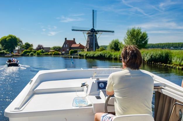 Familienurlaub, sommerferienreise auf lastkahnboot im kanal, mann durch lenkrad auf flusskreuzfahrt im hausboot in den niederlanden