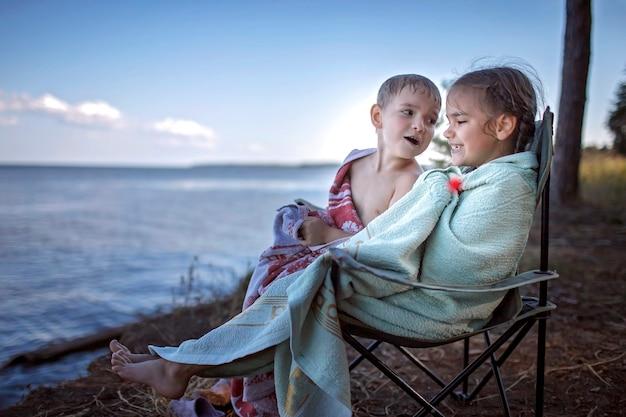 Familienurlaub vor ort. kinder, die das meer nass betrachten, nachdem sie auf campingplatz schwimmen, aktiver lebensstil
