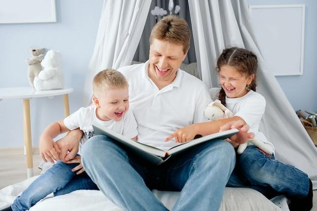 Familienvater liest kindern in einem auf dem boden sitzenden spielzimmer ein lustiges buch vor, kinder und vater lachen emotional