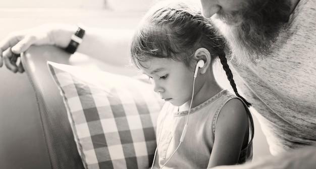 Familienvater-tochter-liebes-parenting-hörendes musik-zusammengehörigkeits-konzept