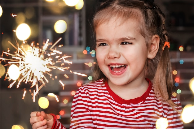 Familienweihnachten zu hause. nettes kleines mädchen in der weihnachtsmütze, die brennende wunderkerze hält und glücklich lächelt