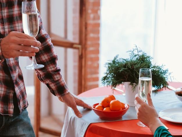 Familienweihnachtsfeier. kurzer schuss des paares, das champagner am festlichen tisch zu hause trinkt.