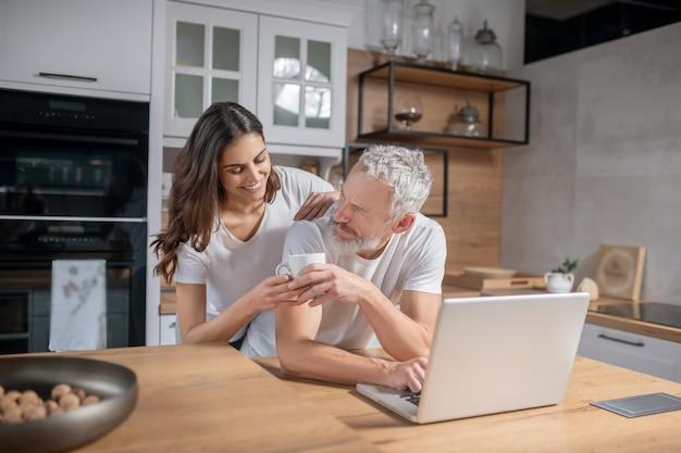 Familienwerte. hübsche junge lächelnde frau, die dem grauhaarigen bärtigen mann, der zu hause am laptop arbeitet, tasse kaffee gibt