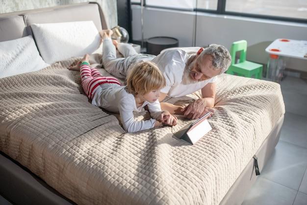 Familienwerte. mann mit kind im schlafanzug, der auf bett zu hause mit tablette ernsthaft interessiert liegt