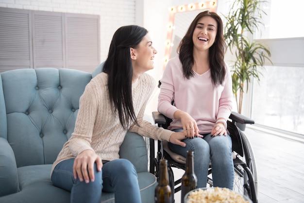 Familienwochenende. begeisterte schwester und behinderte frau kommunizieren und lachen Premium Fotos